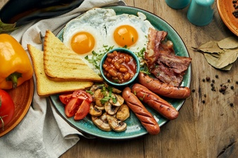 classic english breakfast toasts smoked sausages bacon fried eggs beans fried toasts blue plate top view horizontal wooden surface 207126 401 - بهترین زمان صرف هر وعده غذایی